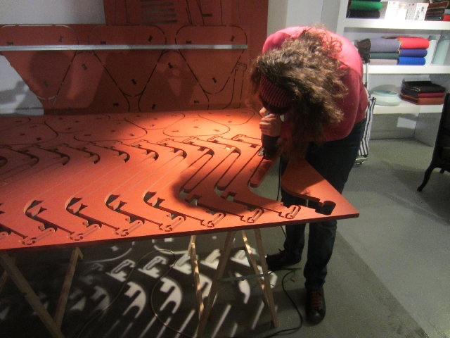 Mariana cutting a Cut Furniture stool